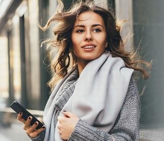 Kobieta ze smartfonem wnioskująca o kredyt